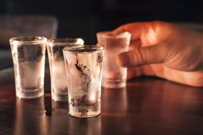Wall mural Shot glass of vodka in hand on a wooden table.