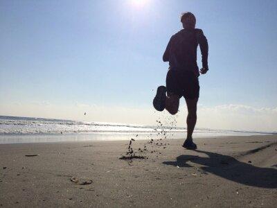 Wall mural Silhoette of man running on beach