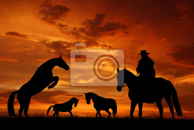 Wall mural Silhouette cowboy with horses in the sunset