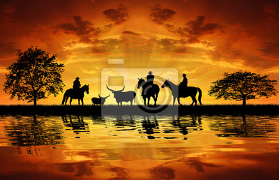 Silhouette cowboys on horses with cows in the sunset