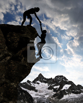Silhouette of girls climbing on rock at sunset