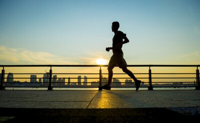 Wall mural Silhouette of jogger running at sunset in front of the city skyline