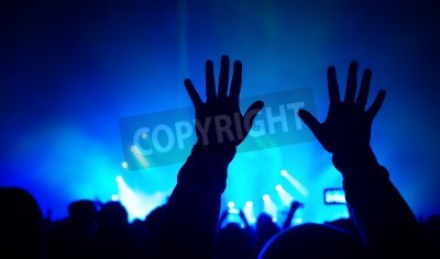 Wall mural Silhouettes of man's hands raised up over crowd of people, enjoying rock concert, bright blue lights, celebrating new year, active night life concept