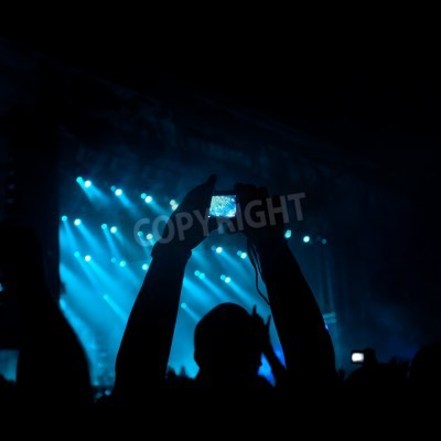 Wall mural silhouettes of people on a rock concert raising hands, stage light in background.NOTE - Some noise and artefacts visible due the use of high ISO because of difficult lighting conditions
