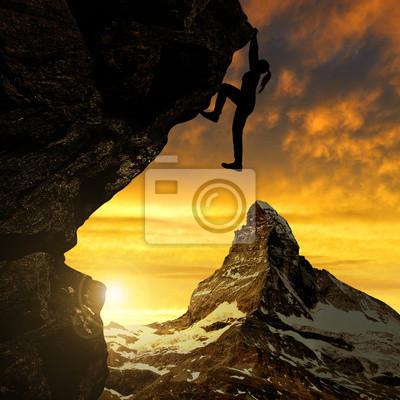 Silhoutte of girl climbing on rock at sunset - Swiss