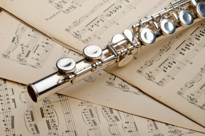 Silver flute on an ancient musical background