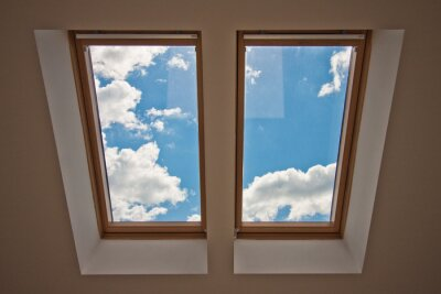Wall mural Skylights. View from the window. View of the sky from the window. Window on the roof. Sunlight through the attic window. Light in the house