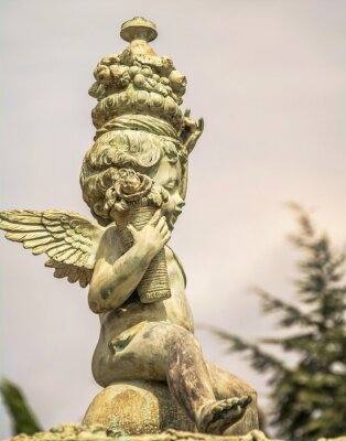 Small plaster garden sculpture of  cute angel with flowers and fruits in hand