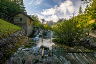 small waterfall on a stream flowing out of Lake Laghi di Fusine in the Julian Alps in Italy