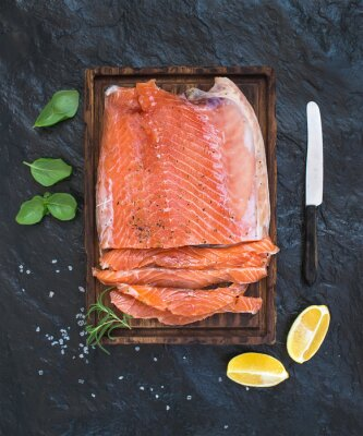 Wall mural Smoked salmon filet with lemon, fresh herbs and bred on wooden serving board over dark stone backdrop