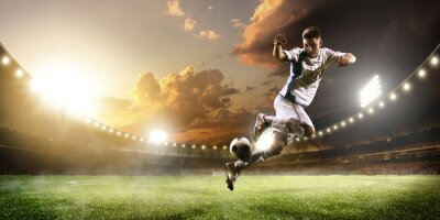 Wall mural Soccer player in action on sunset stadium panorama background
