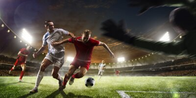 Wall mural Soccer players in action on sunset stadium background panorama