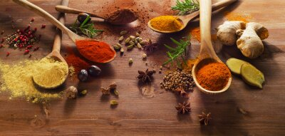 Wall mural Spices and herbs on wooden table.