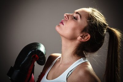 Wall mural Sport boxer woman in black gloves boxing