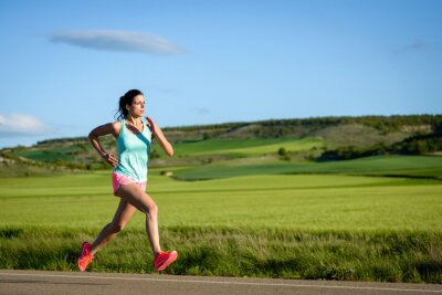 Wall mural Sporty woman running fast on country side road. Female athlete training outdoor.