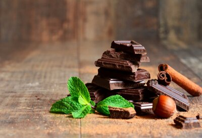 Wall mural Stack of chocolate slices with mint leaf,hazelnut and cinnamon.