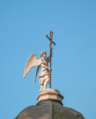 Statue of  angel with  cross in his hands on  dome of  old church