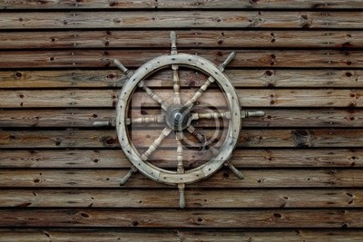 Steering wheel of the ship on a wooden wall