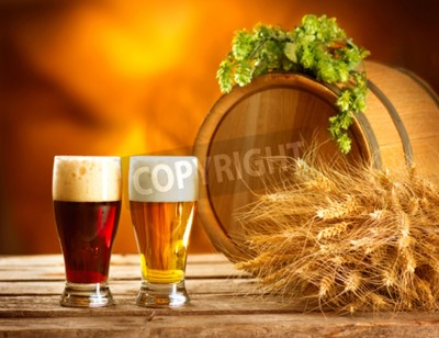 Wall mural Still life composition with Vintage beer barrel and two glasses of dark and light beer. Fresh amber beer concept. Green corns of hop and wheat on wooden table. Ingredients for brewery. Brewing traditi