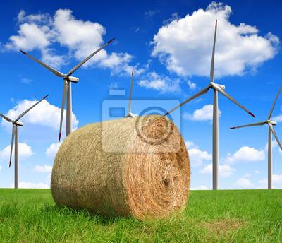Straw bale on farmland with wind turbines