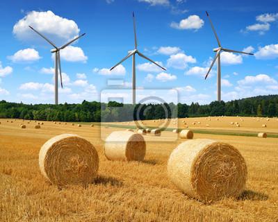 Straw bales on farmland on the background wind turbines