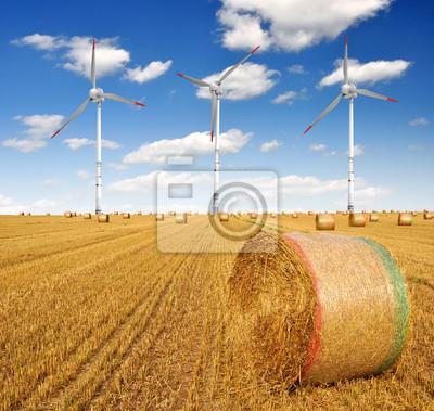 Straw bales on farmland with wind turbine