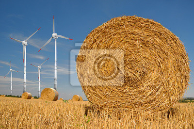 Straw bales on farmland with wind turbine on blue cloudy sky