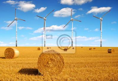 Straw bales on farmland with wind turbines