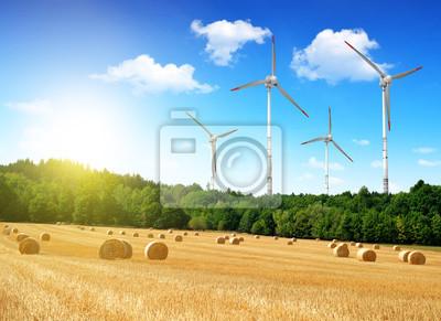 Straw bales with wind turbines on farmland
