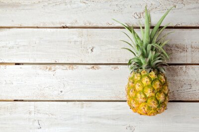 Wall mural Summer background with pineapple on wooden board