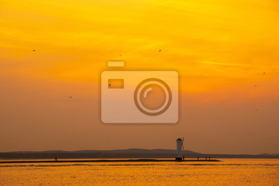 sunset over a lighthouse .Swinoujscie, Poland