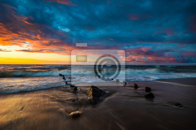 sunset over the sea beach in Poland, waves dynamically breaking into the beach
