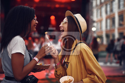 Wall mural Taste this. Side view portrait of lovely girl in hat holding for with french fry while her friend looking at it and smiling