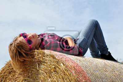 The girl lying on the straw bale