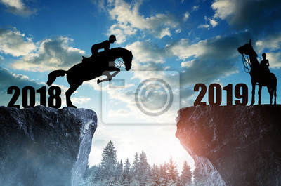 The rider on the horse jumping into the New Year 2019 at sunset.