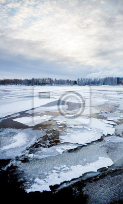 Thin ice and chunks of ice on a lake at sunrise
