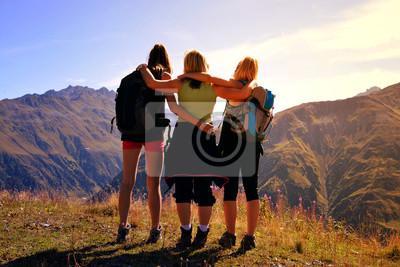 Three tourists looks at the alpine landscape in the Canton Graubunden - Switzerland.