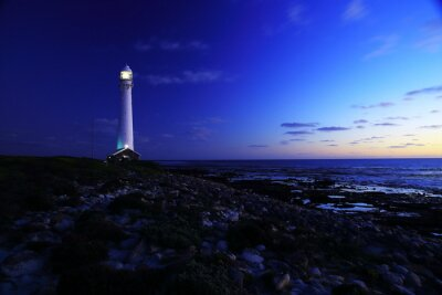 Wall mural To the lighthouse / An evening view of the Slangkop Lighthouse with rocks and clouds