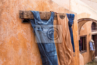Wall mural Tone on tone dresses on a clothes hook on an orange warm wall