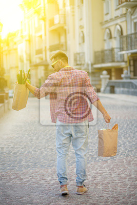 Wall mural Toned image. Profile of young man's back in sunglasses. Handsome man lifting bag full of food with his left hand. Toned image.