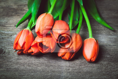 Wall mural Toned photo. Color tone tuned. Bouquet of Red fresh tulips (border design) on wood table