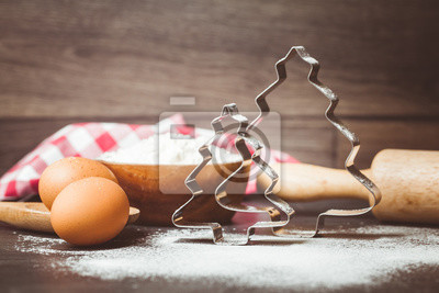 Wall mural Toned photo. Color tone tuned. Cookie cutters in shape of christmas tree, egg, wooden spoon, rolling pin for cookies and gingerbread, accessories for baking, christmas time