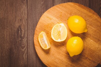 Wall mural Toned photo. Color tone tuned. Fresh lemons on wooden cutting board, top view