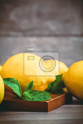 Wall mural Toned photo. Color tone tuned. Glass with water and lemon on vintage wooden table