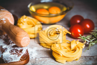 Wall mural Toned photo. Color tone tuned. Homemade tagliatelle. Raw pasta on the wooden table. Selective focus.