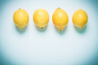 Wall mural Toned photo. Color tone tuned. Top view of four lemons on blue background