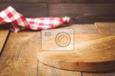 Wall mural Toned photo. Color tone tuned. Wooden background with wooden table, tablecloth and round cutting board