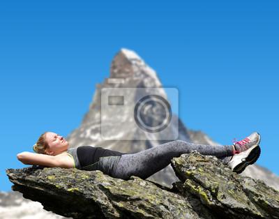 Tourist lying on a rock, in the background mountain Matterhorn - Swiss Alps, Europe