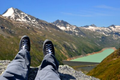 Tourist on a trip in Alps in the Swiss canton of Valais. In the background dam of Mattmark.