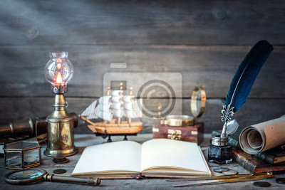 Travel and nautical theme grunge background. Old book, compass, telescope, divider, coins, shell, map, hourglass, quill pen on wood desk. Columbus Day.